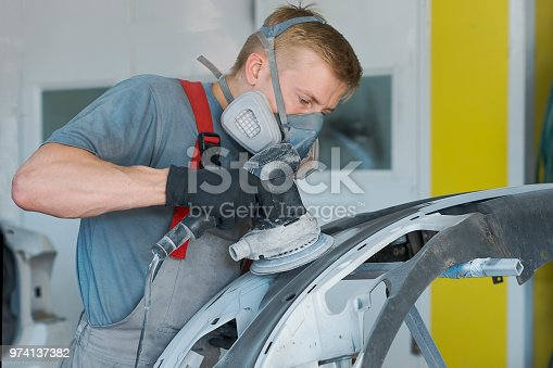 istock Auto mechanic restores car body part after car accident 974137382