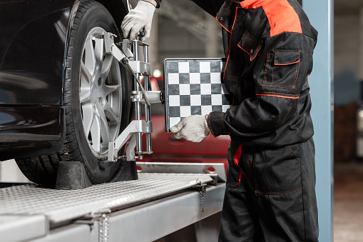 auto mechanic sets the car for diagnostics and configuration. Wheel alignment equipment on a car wheel in a repair station.