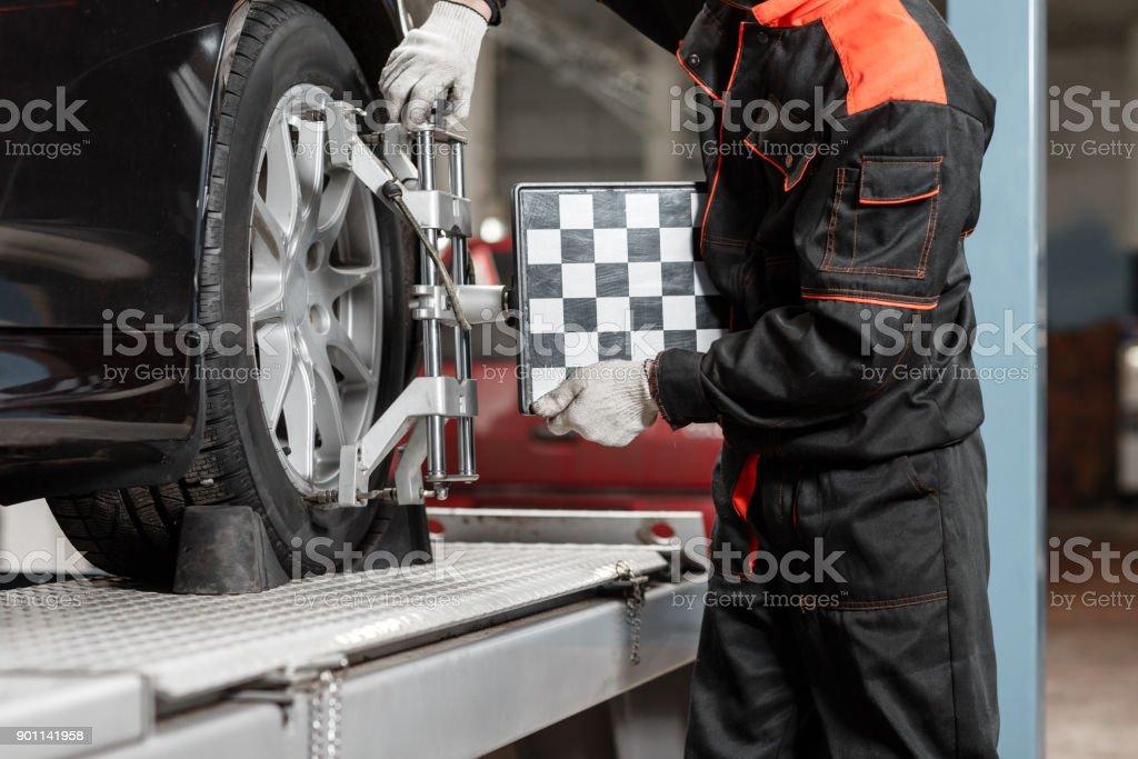Kfz-Mechaniker legt das Auto für Diagnose und Konfiguration. Rad Achse Ausrüstung auf einem Auto-Rad in eine Reparaturstation – Foto