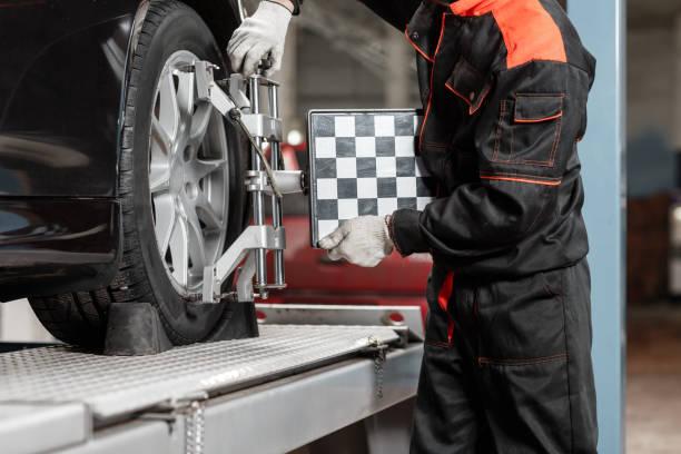 자동차 정비사는 진단 및 구성에 대 한 자동차를 설정합니다. 수리 역에서 자동차 바퀴에 바퀴 정렬 장비 - 정돈 뉴스 사진 이미지