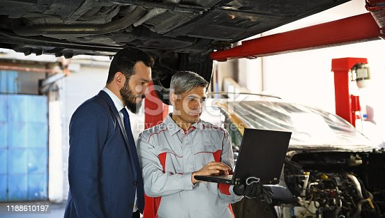 136591855 istock photo Auto Mechanic Showing Data on the Computer 1188610197