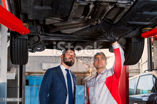 136591855 istock photo Auto Mechanic Showing the Problem Under the Car 1186850502