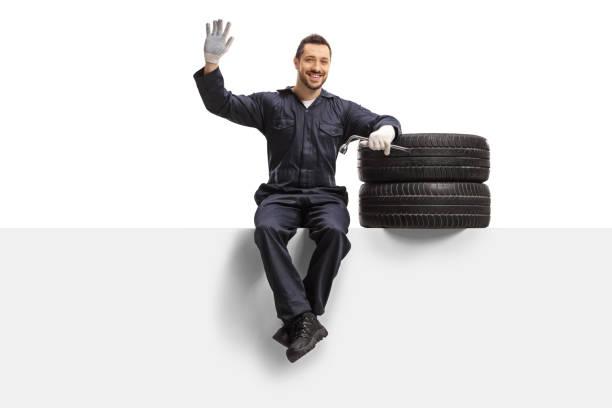mécanicien automatique s'asseyant sur un panneau avec des pneus et une clé et agitant à l'appareil-photo - homme faire coucou voiture photos et images de collection