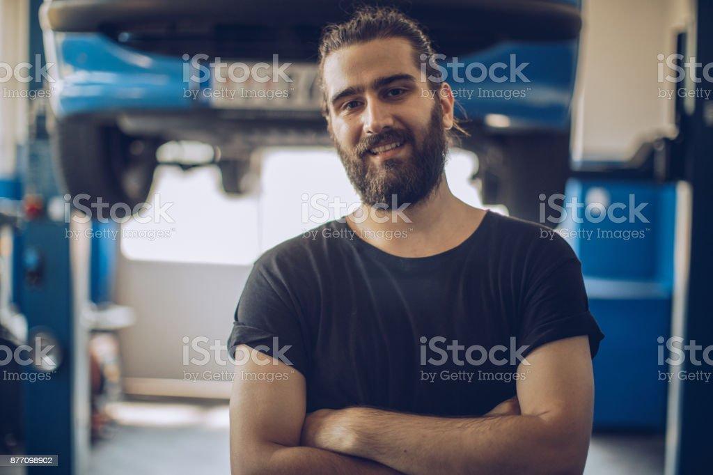 Auto Mechanic standing in workshop stock photo
