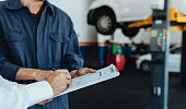 Mechanic taking sign on document from customer in garage. Hands of car service client signing papers after getting his car repaired.