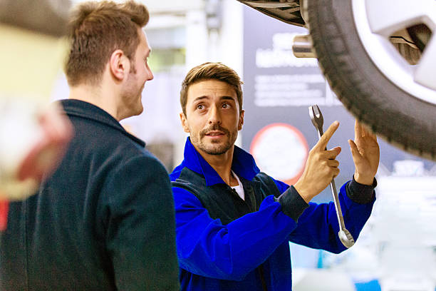 Auto Mechanic Talking With Car Owner stock photo