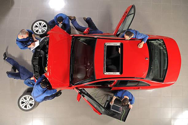 Auto mechanic team repairing the sports car
