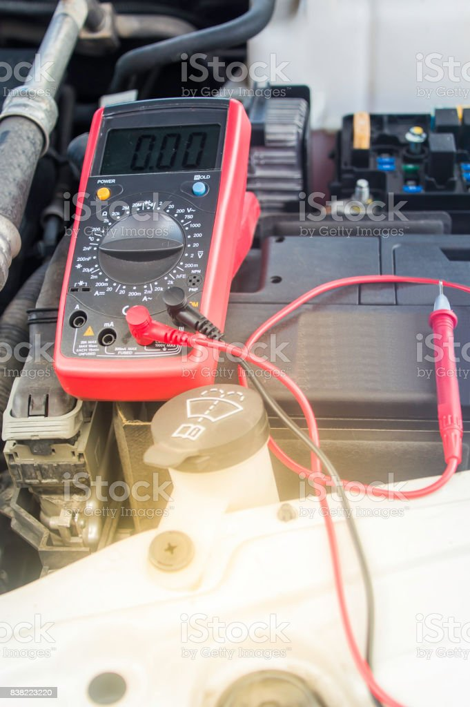Auto Mechanic Uses A Multimeter Voltmeter To Check The Voltage Level
