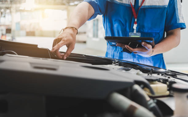 Auto mechanic uses the tablet to check. Auto mechanic are checking the condition of the car according to the month. The technician uses the tablet to check. mechanic stock pictures, royalty-free photos & images