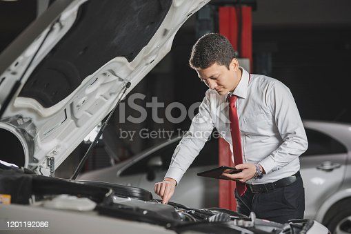 1137474295 istock photo Auto mechanic uses the tablet to check. 1201192086