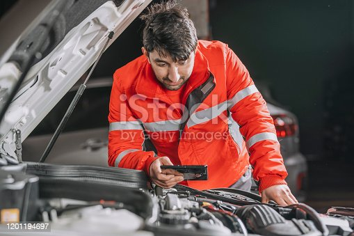 1137474295 istock photo Auto mechanic uses the tablet to check. 1201194697
