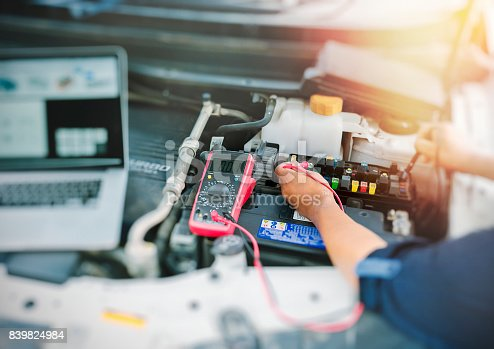 istock Auto mechanic using digital multimeter. 839824984