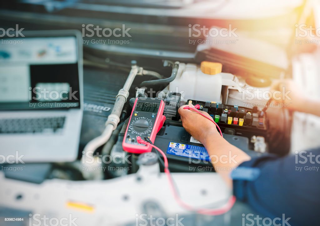 Auto mechanic using digital multimeter. stock photo