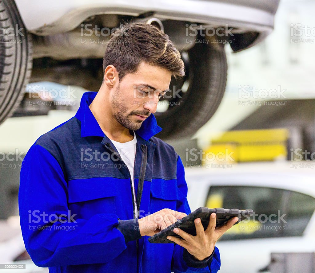 Auto Mechanic Using Digital Tablet stock photo