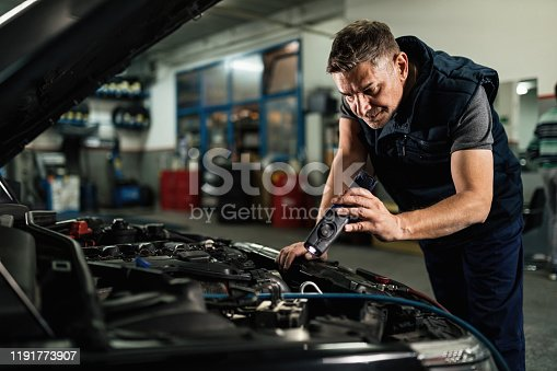 Mid adult mechanic examining car engine while using a lamp in auto repair shop.