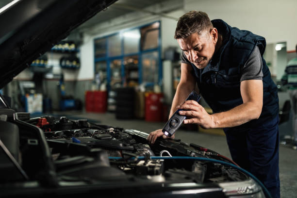 Auto mechanic using lap while examining car engine in repair shop. Mid adult mechanic examining car engine while using a lamp in auto repair shop. engine stock pictures, royalty-free photos & images