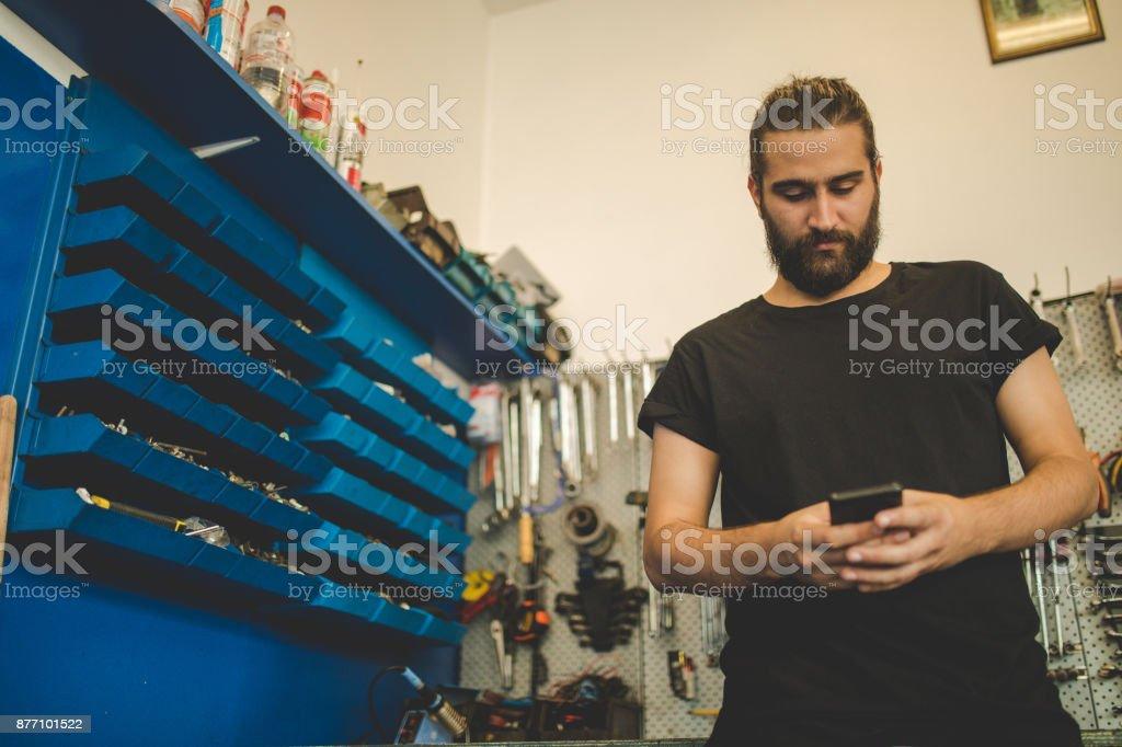 Auto Mechanic using phone stock photo
