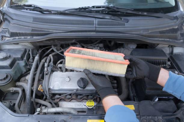 Automechaniker trägt Schützenhandschuhe, die gebrauchten Luftfilter über einem Automotor halten – Foto