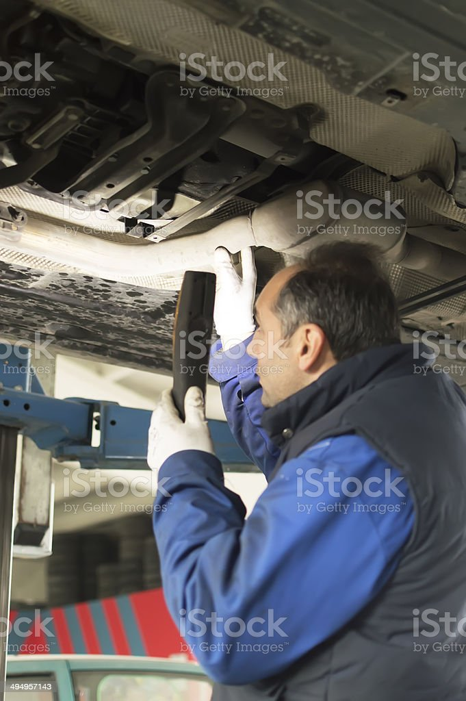 auto mechanic who looks under a car for inspection royalty-free stock photo