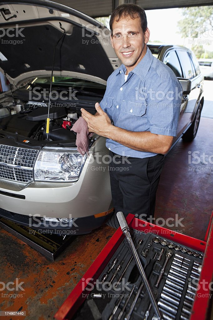 Auto mechanic wiping hands stock photo