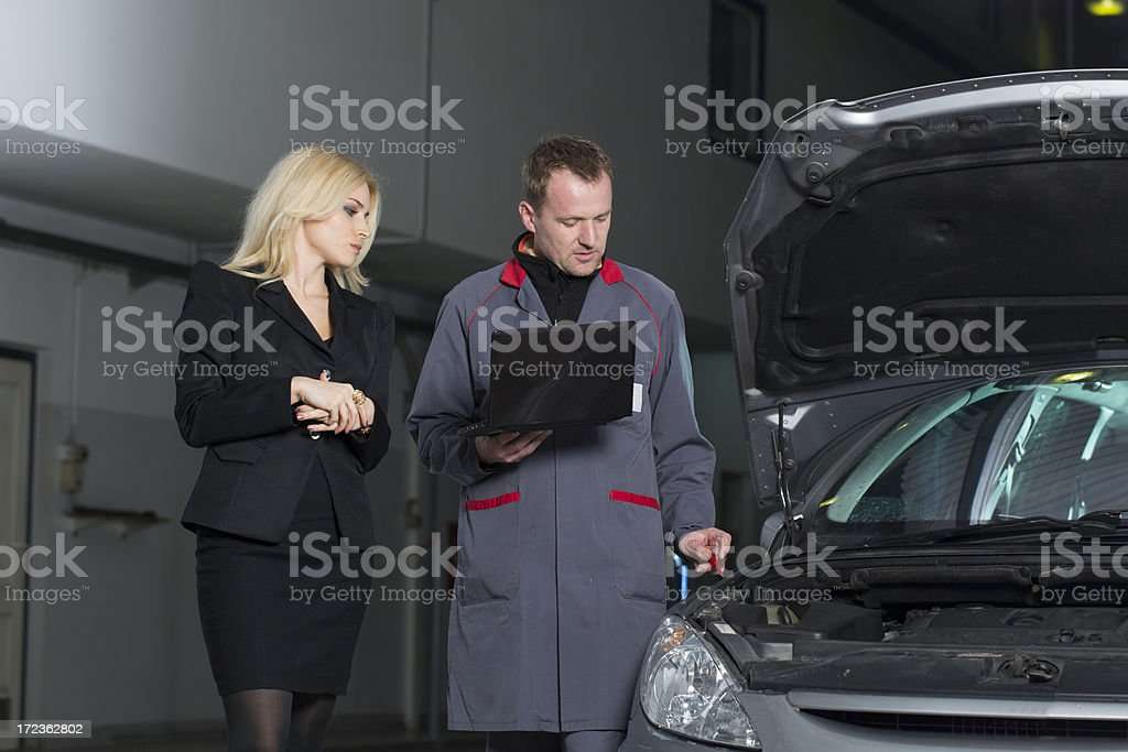 Auto mechanic with digital tablet talking to a customer royalty-free stock photo