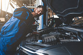 istock Auto mechanic with wrench over car hood. Car repairman in the service garage 1254065794