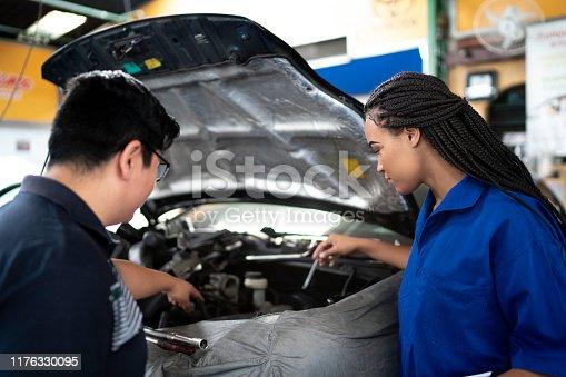 Auto mechanic woman doing a customer checklist in auto repair shop