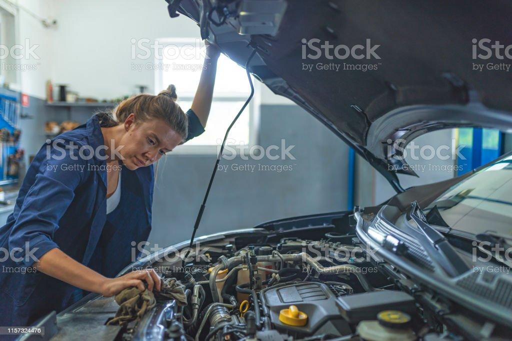 Auto car repair service center. Mechanic examining car engine. Female...