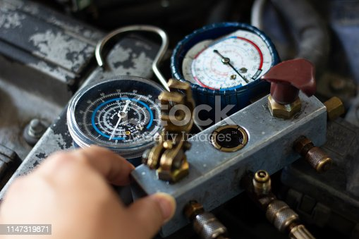 istock Auto mechanic worker fixing air condition in car garage . Monitoring tools check car air conditioner system.Vehicle engine maintenanceservice, Repair Engine pressure measurement system. 1147319871