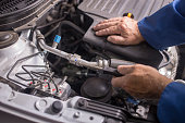 istock Auto mechanic working in garage. Car service, Repair and maintenance. Hand holding wrench 1045290928