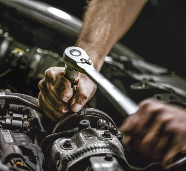Auto mechanic working in garage. Repair service. stock photo