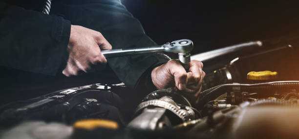 Auto mechanic working in garage. Repair service. Auto mechanic working on car engine in mechanics garage. Repair service. authentic close-up shot mechanic stock pictures, royalty-free photos & images