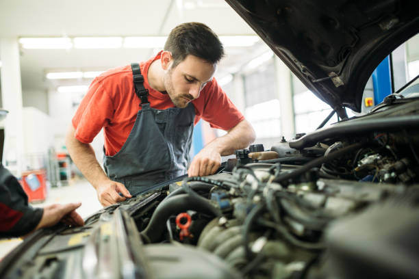 Auto mechanic working in garage. Repair service. Young auto mechanic working in garage. Repair service. repairman stock pictures, royalty-free photos & images