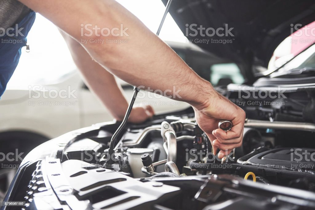Auto mechanic working in garage. Repair service Close up hands of unrecognizable mechanic doing car service and maintenance. Adjusting Stock Photo