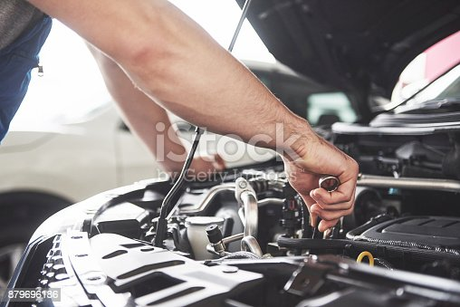 istock Auto mechanic working in garage. Repair service 879696186