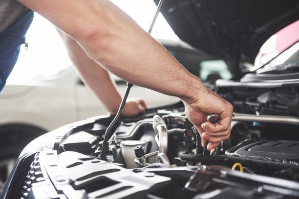 Auto mechanic working in garage. Repair service Close up hands of unrecognizable mechanic doing car service and maintenance. repairman stock pictures, royalty-free photos & images