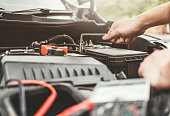 istock Auto mechanic working in garage Technician Hands of car mechanic working in auto repair Service and Maintenance car battery check. 1089940430