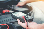 istock Auto mechanic working in garage Technician Hands of car mechanic working in auto repair Service and Maintenance car battery check. 1089940440