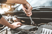 istock Auto mechanic working in garage Technician Hands of car mechanic working in auto repair Service and Maintenance car check. 1089940482