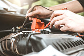 istock Auto mechanic working in garage Technician Hands of car mechanic working in auto repair Service and Maintenance car battery check. 1089940486