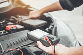 istock Auto mechanic working in garage Technician Hands of car mechanic working in auto repair Service and Maintenance check car battery. 1134371598