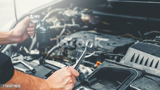 istock Auto mechanic working in garage Technician Hands of car mechanic working in auto repair Service and Maintenance car check. 1134371623