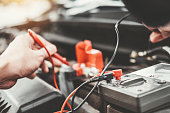 istock Auto mechanic working in garage Technician Hands of car mechanic working in auto repair Service and Maintenance check car battery. 1152944651