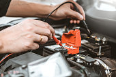 istock Auto mechanic working in garage Technician Hands of car mechanic working in auto repair Service and Maintenance check car battery. 1152944654