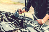 istock Auto mechanic working in garage Technician Hands of car mechanic working in auto repair Service and Maintenance car check. 1169927983