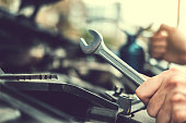istock Auto mechanic working in garage Technician Hands of car mechanic working in auto repair Service and Maintenance car check. 1169927985