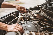 istock Auto mechanic working in garage Technician Hands of car mechanic working in auto repair Service and Maintenance car check. 1169927997