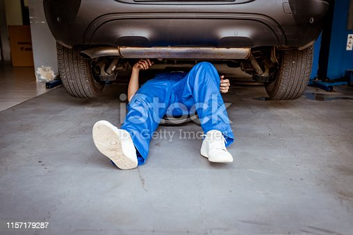 Unrecognizable Person, Mechanic lying and working under car at the repair garage. Mechanic in blue uniform lying down and working under car at the auto service garage. Young mechanic lying down and working under car at the garage. Repair undercarriage service.