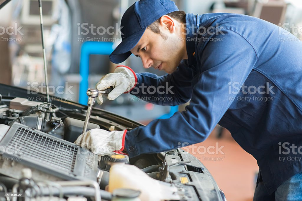 Auto mechanic working on a car in his garage stock photo