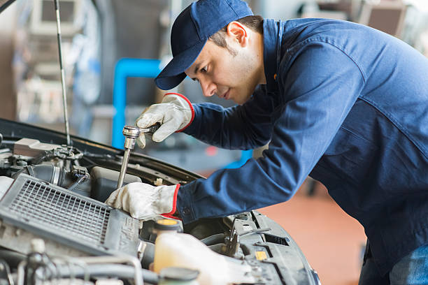 Auto mechanic working on a car in his garage Auto mechanic working on a car in his garage mechanic stock pictures, royalty-free photos & images